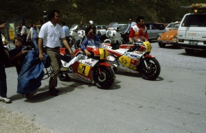 Spencer's chief engineer Erv Kanemoto and mechanic George Vukmanovich walk the V4 NSR500 back from the pits in Austria.